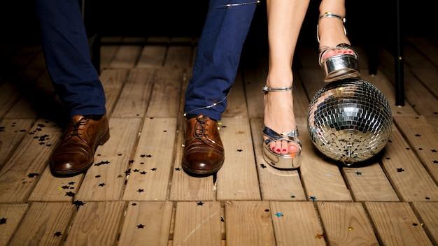 Couple debout sur un plancher en bois avec boule disco