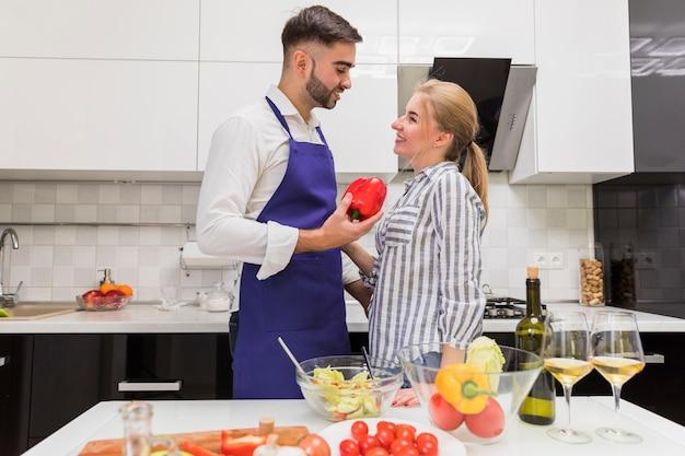 Couple, debout, à, poivron rouge, près, table