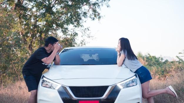 Couple debout prendre une photo avec une voiture