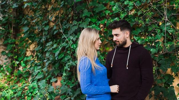 Couple debout près du mur avec des feuilles vertes