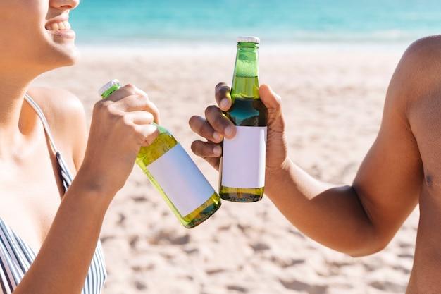Couple debout sur le rivage et bouteille de boisson