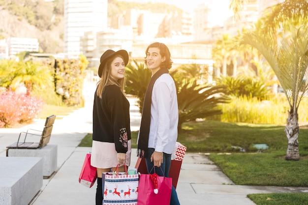 Couple debout avec des sacs de shopping de noël