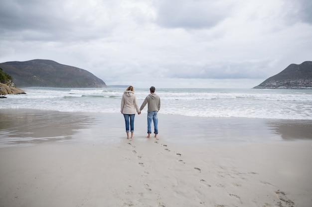 Couple, debout, tenue, mains, plage
