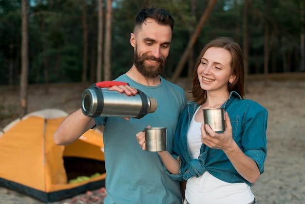 Couple debout versant du thé et souriant