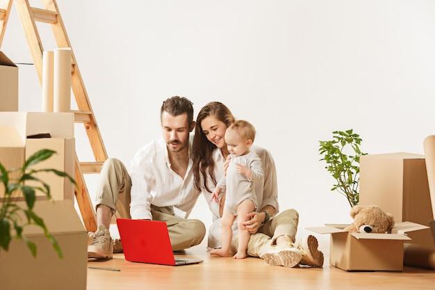 Couple déménageant dans une nouvelle maison. des personnes mariées heureuses avec un nouveau-né achètent un nouvel appartement pour commencer la vie ensemble. la famille au rabotage de réparation et de relocalisation à l'hébergement contre des boîtes