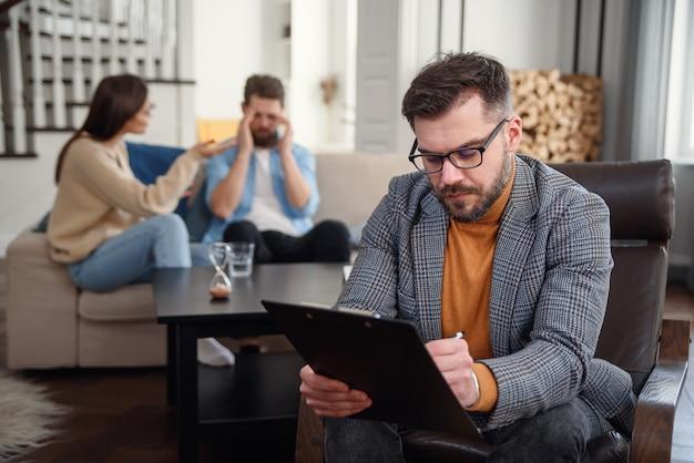 Un couple déprimé est assis sur un canapé et se dispute entre eux pendant que le psychologue prend des notes.