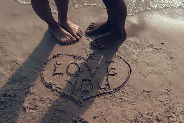 Couple dessine une image du cœur avec le signe 'love you' sur le sable