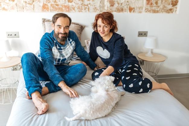 Couple détendu à la maison au lit avec le chien