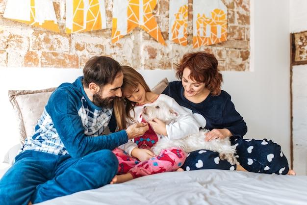 Couple détendu à la maison au lit avec leur petite fille et le chien