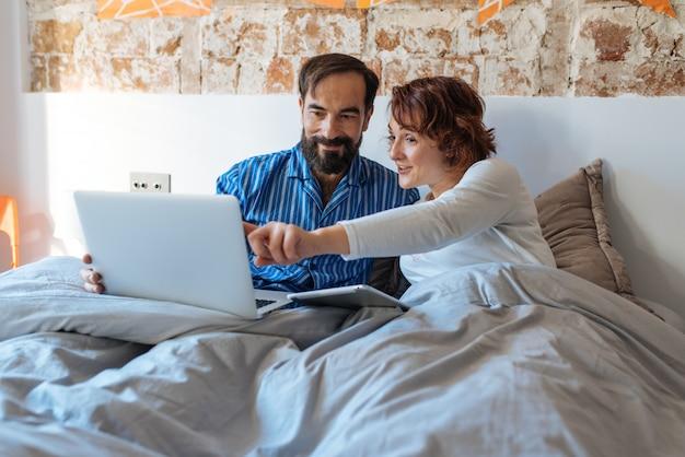 Couple détendu à la maison au lit sur l'ordinateur et la tablette
