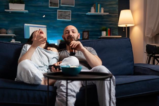 Couple détendu en pyjama se reposant sur un canapé en train de manger du pop-corn en regardant un film comique