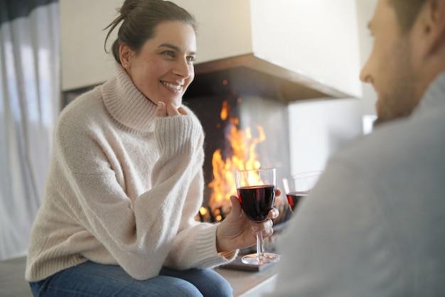 Couple de détente au coin du feu en dégustant un verre de vin rouge