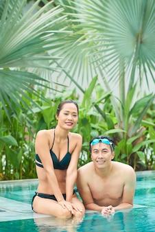 Couple de détente dans la piscine de l'hôtel