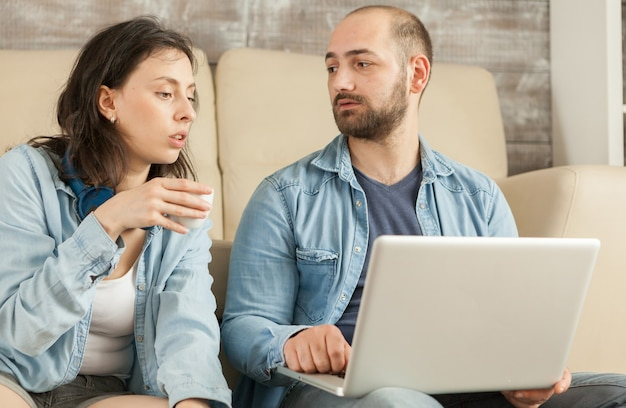 Couple de détente dans le salon en buvant du café et en naviguant sur internet