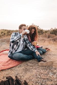 Couple de détente en plein air à côté d'un feu de camp