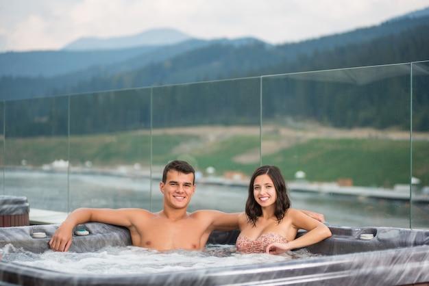 Couple de détente en profitant jacuzzi bain à remous bain moussant
