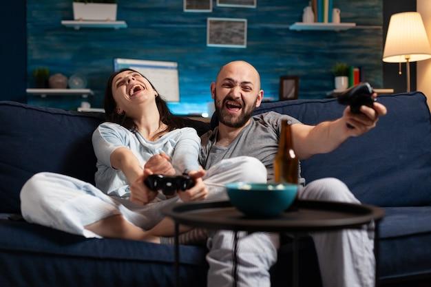Couple déterminé et concentré jouant au jeu vidéo de football tard dans la nuit