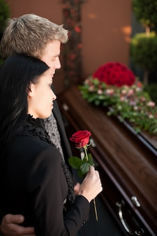 Couple en deuil à l'enterrement avec cercueil