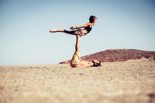Couple de deux adultes et personnes ensemble à la plage s'entraînant ensemble sur le sable faisant des positions de yoga avec des collines en arrière-plan
