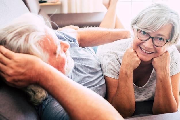 Couple de deux personnes âgées en couple et mariées allongées sur le canapé ensemble - femme regardant l'homme souriant - amour et affection
