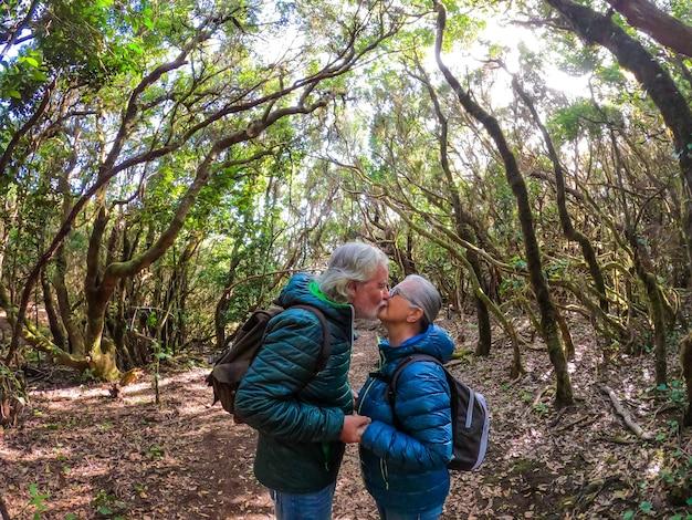 Couple de deux personnes âgées heureuses et en bonne santé et de personnes mûres dans une randonnée en forêt et marchant ensemble - un homme et une femme retraités s'embrassant avec les arbres en arrière-plan