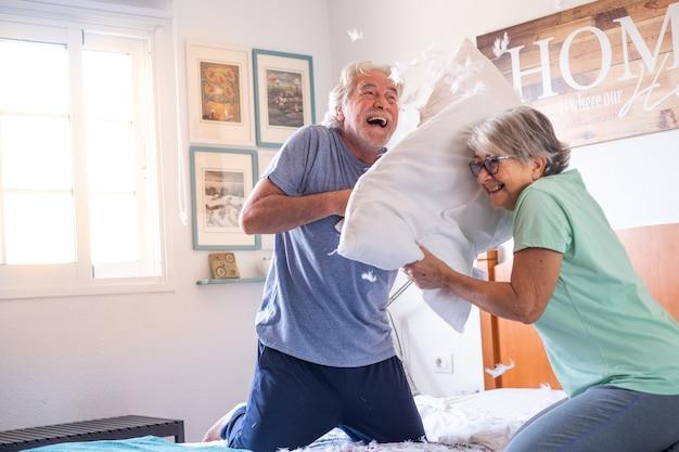 Couple de deux personnes âgées heureuses s'amusant à jouer ensemble sur le lit à la maison se battant avec des oreillers appréciant - la guerre des oreillers à l'intérieur le matin