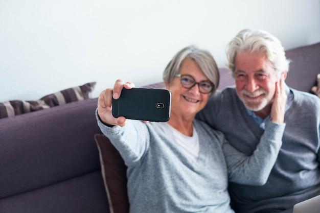 Couple de deux personnes âgées à la maison sur le canapé prenant un selfie ensemble - personnes mûres souriant et regardant la caméra du téléphone pour prendre une photo