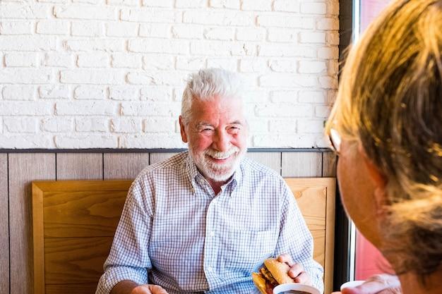 Couple de deux personnes âgées mangeant et buvant dans un restaurant de restauration rapide ensemble - homme mûr tenant un hamburger et prêt à le manger en regardant sa femme