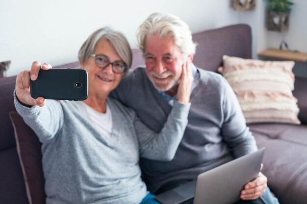 Couple de deux personnes âgées ou matures sur le canapé avec leur ordinateur portable et prenant un selfie avec son téléphone - personnes âgées de race blanche