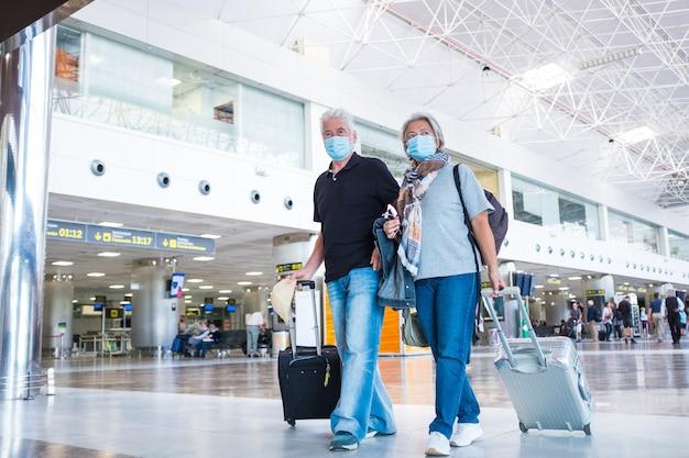 Couple de deux personnes âgées ou matures marchant dans l'aéroport pour se rendre à leur porte et prendre leur vol avec un masque médical pour prévenir les virus comme le coronavirus ou le covid-19 - transportant des bagages ou un chariot