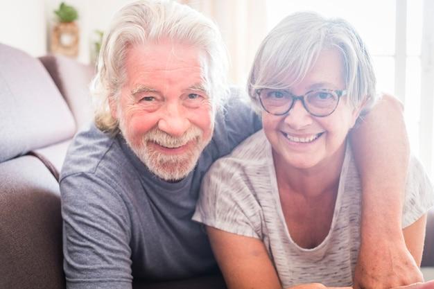 Couple de deux personnes âgées et personnes mûres allongées sur le canapé regardant la caméra en souriant et en riant - mariés avec vivre pour toujours à la maison
