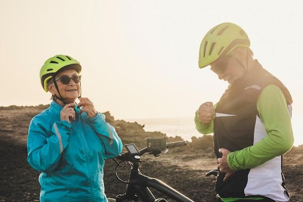 Couple de deux personnes âgées ou personnes mûres donnant cinq avec leurs mains ensemble - amitié de deux retraités faisant de l'exercice ensemble