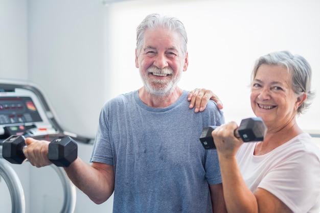 Couple de deux personnes âgées à la salle de sport tenant des haltères et avec le tapirulan en arrière-plan - personnes matures actives faisant des exercices ensemble
