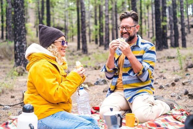 Couple de deux personnes heureuses et un chien mangeant ensemble faisant un pique-nique au sol dans la montagne avec beaucoup d'arbres autour d'eux