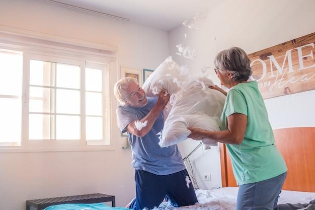 Couple de deux seniors heureux et actifs jouant et se battant ensemble dans la chambre sur le lit s'amusant à la maison le matin - concept de mode de vie sain