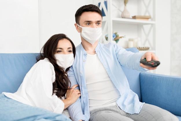 Couple devant la télé à la maison avec des masques