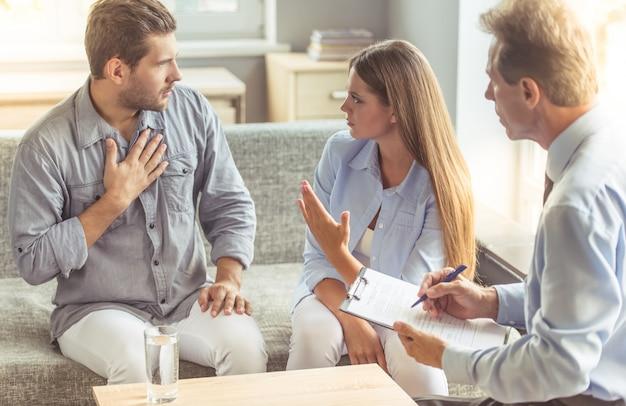 Un couple discute assis sur un canapé chez un psychothérapeute.