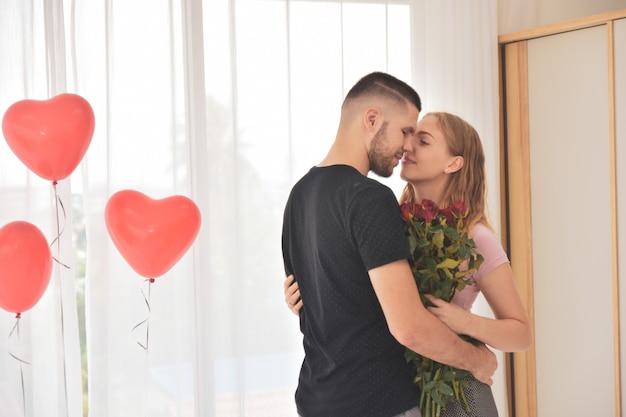 Couple, donner, fleur rose, dans, chambre à coucher, bonheur, dans, saint valentin, foyer sélectif