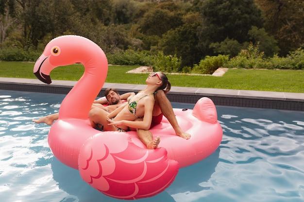 Couple, dormir ensemble, sur, a, gonflable, tube, dans, piscine