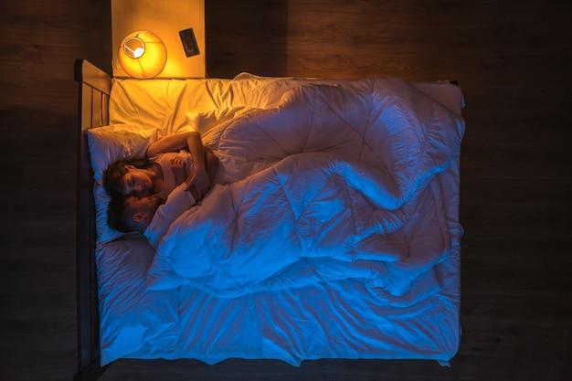 Le couple dort sur le lit. le soir la nuit. vue d'en-haut