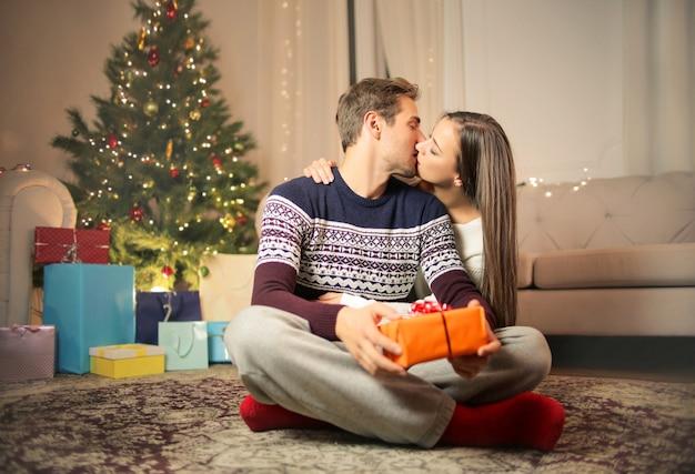 Couple doux ouvrant ensemble des cadeaux de noël