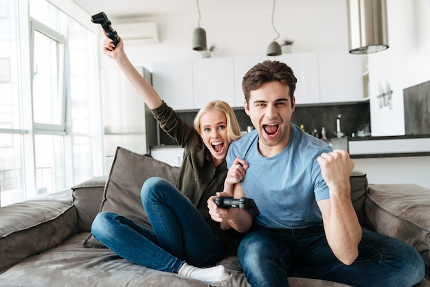 Couple drôle, jouer à des jeux vidéo et regarder la caméra