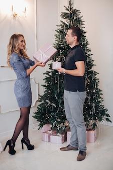 Couple échangeant des cadeaux à noël.