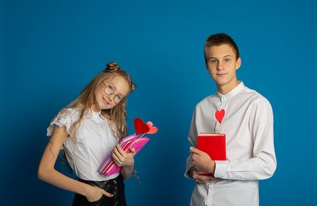 Un couple d'écoliers sont des adolescents le jour de la saint-valentin sur fond bleu