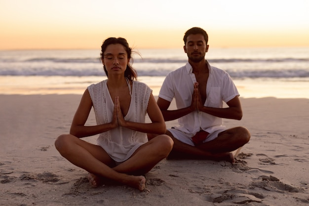 Couple effectuant le yoga ensemble sur la plage