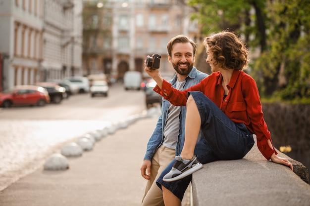 Couple élégant amoureux assis dans la rue lors d'un voyage romantique, prenant une photo