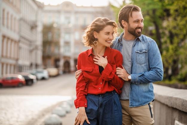 Couple élégant amoureux assis dans la rue en voyage romantique