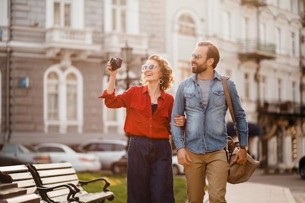 Couple élégant amoureux marchant embrassant dans la rue lors d'un voyage romantique et prenant des photos
