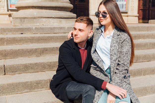 Couple élégant assis dans les escaliers et regardant dans une direction
