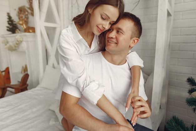 Couple élégant assis sur un lit près de l'arbre de noël